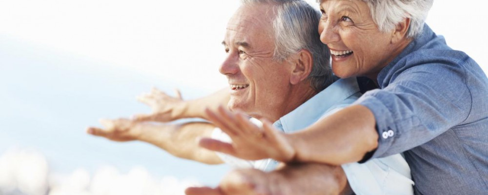Cheerful mature couple smiling while enjoying outdoors with arms outstretched